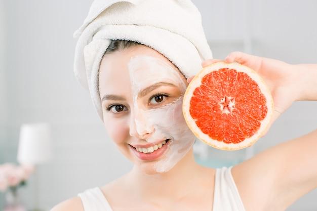 Портрет молодой красивой женщины с здоровой свечение идеально гладкой кожи держит кусок грейпфрута, белое полотенце на голове, белая маска на лице. натуральная косметика, уход за кожей, концепция ухода за лицом.