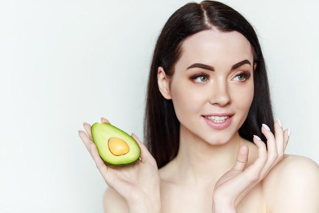 Портрет молодой красивой женщины со здоровой кожей держит авокадо