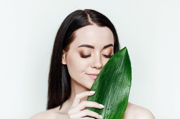 Портрет молодой красивой женщины со здоровой кожей держит зеленый тропический лист