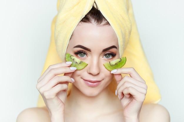 Портрет молодой красивой женщины со здоровой кожей держит кусок киви возле лица.