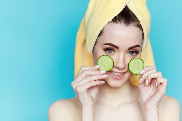 健康な肌を持つ若い美しい女性の肖像画は、顔の近くにキュウリの2つの部分を保持します。
