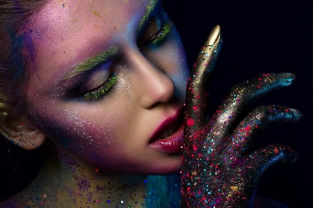 Портрет молодой красивой женщины с составом современной моды творческим. подиум или макияж на хэллоуин. студийный снимок