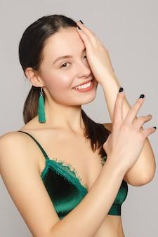 手入れの行き届いた指で彼女の顔に触れる完璧な肌と明るいメイクの若い美しい女性の肖像画。彼女の耳に長い緑色の布のイヤリング。彼女の肩は裸。閉じる。コピースペース