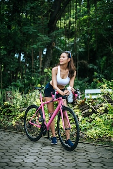 Portrait of young beautiful woman with pink bike in the park. Actractive healthy woman.
