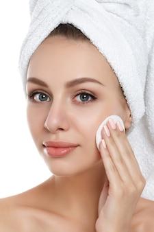 고립 된 화장품 패드와 함께 그녀의 얼굴에서 메이크업을 청소하는 그녀의 머리에 수건으로 아름 다운 젊은 여자의 초상화. 얼굴 청소, 완벽한 피부, 스킨 케어 및 미용 컨셉