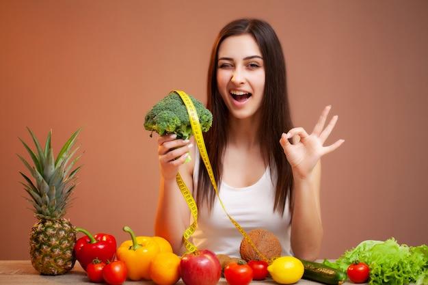 Портрет молодой красивой женщины с овощами, фруктами и измерительной ленты