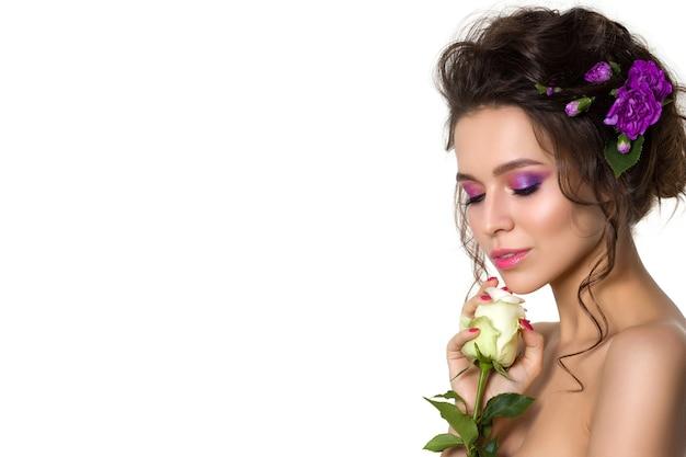 포즈를 취하는 그녀의 머리에 보라색 꽃을 가진 아름 다운 젊은 여자의 초상화. 여자 내려다보고 흰색 장미를 만지고. 밝은 여름 패션 메이크업. 핑크색 입술과 스모키 눈.