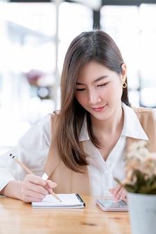 Портрет молодой красивой женщины, писать на ноутбуке и с помощью смартфона, сидя за офисным столом.