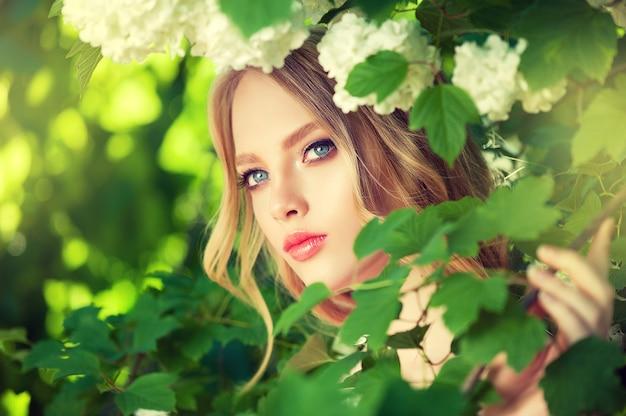 影の新鮮な緑の庭の木、彼女の長い巻き毛のブロンドの髪の弱い風の中で若い美しく見えるモデルの肖像画。女性の美しさと若さの花。メイクアップとヘアスタイリング。