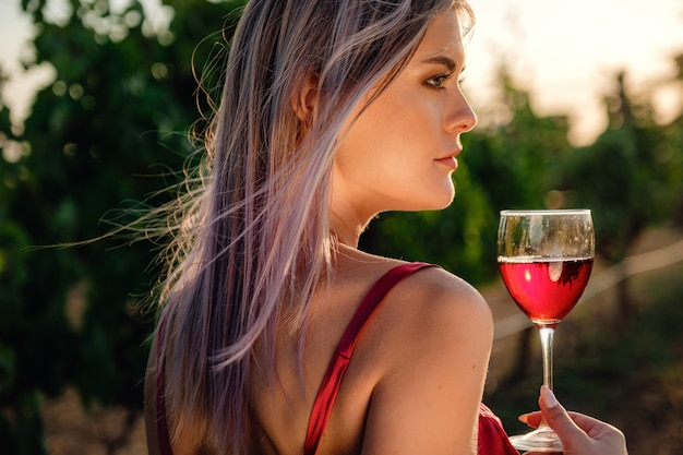 Портрет молодой дамы красоты в красном платье на виноградниках в летний сезон. наслаждайтесь дегустационным туром по чудесному винодельческому региону.