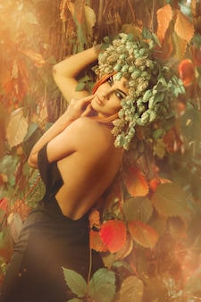 森の中で屋外の頭にホップを持つ若い美しい少女の肖像画
