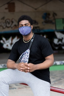 얼굴 마스크와 젊은 흑인 소년의 초상화입니다. 낙서 벽 배경입니다.