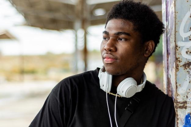白いヘッドフォンで若い黒人少年の肖像画。音楽を聴く。放棄された建物の背景。