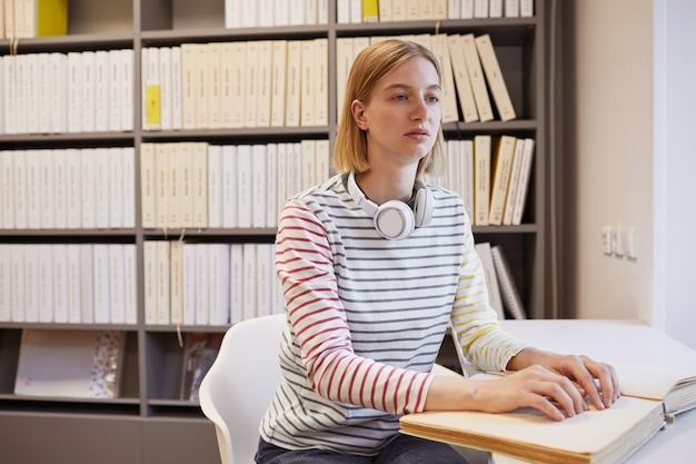 大学図書館のコピースペースで点字本を読んでいる若い盲目の女性の肖像画