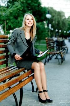 Портрет молодой белокурой дамы в официальной деловой одежде, сидящей на скамейке в парке с документами чтения в летний ясный день. концепция красивая современная бизнесвумен