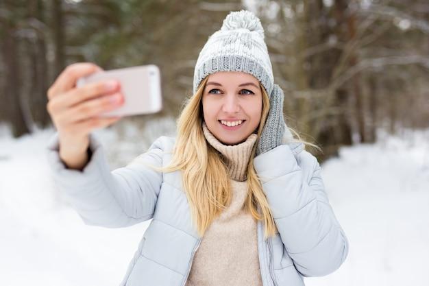 冬の公園や森でスマートフォンでselfie写真を撮る若いブロンドの女性の肖像画