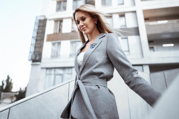 도시에서 걷는 회색 양복에 젊은 금발 사업가의 초상화