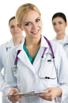 Портрет молодой блондинки женщина-врач, держащая файл с документами в окружении медицинской бригады, глядя и улыбаясь. концепция здравоохранения и медицины.