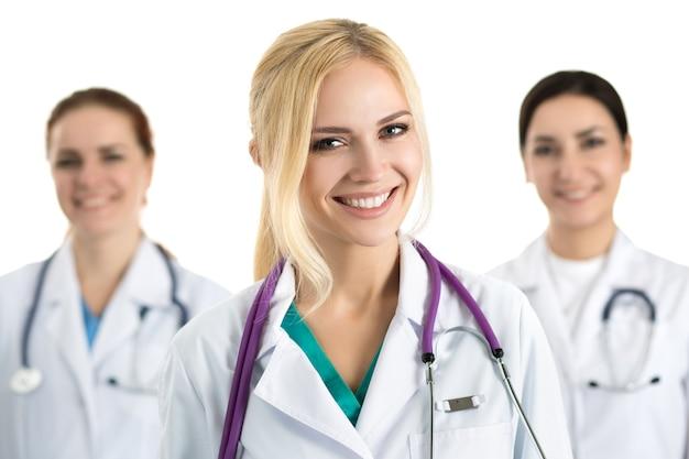 Портрет молодой блондинки женщины-врача в окружении медицинской бригады, глядя и улыбаясь. концепция здравоохранения и медицины.