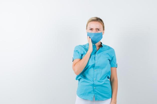 カジュアルな服装で歯痛に苦しんでいる若い金髪女性の肖像画