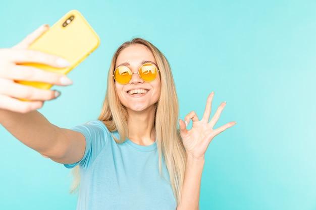 青で隔離のフロントカメラでselfieを撮影スマートフォンを手に持ってビデオ通話を持っている若いブロンドの女の子の肖像画。