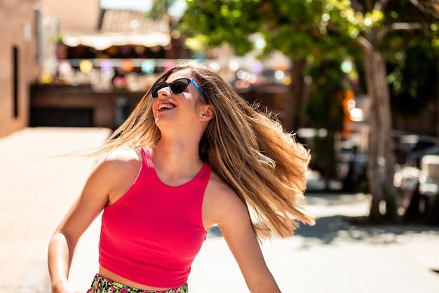 긴 머리와 선글라스 행복 하 고 춤 젊은 금발 소녀의 초상화. 초점 컬러 조명의 배경입니다.