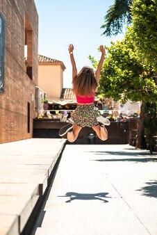 긴 머리와 선글라스 점프 젊은 금발 소녀의 초상화. 초점 컬러 조명의 배경입니다.