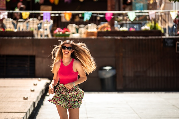 긴 머리와 선글라스 실행 젊은 금발 소녀의 초상화. 초점이 조명 색상의 배경입니다.