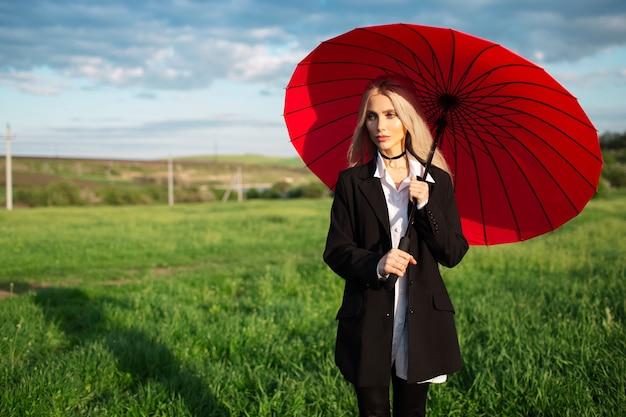 Портрет молодой блондинки красивой девушки в черно-белом костюме, держа красный зонтик на фоне облачного неба и зеленого поля.