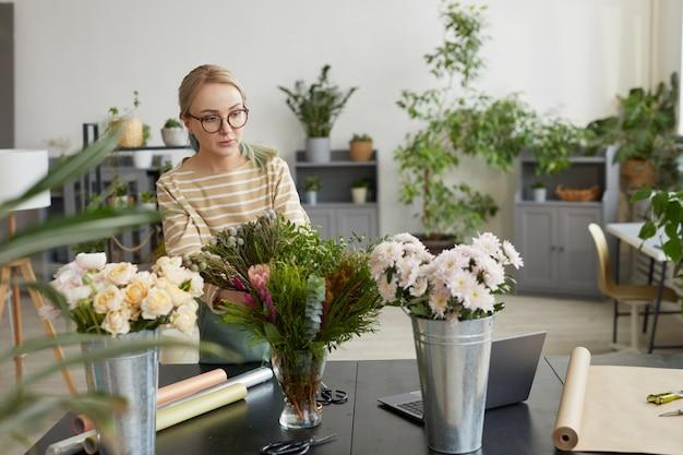 Портрет молодой блондинки, собирающей букеты во время работы в мастерской зеленых флористов, копией пространства