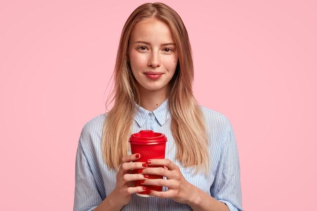 一杯のコーヒーを保持している若いブロンドの女性の肖像画