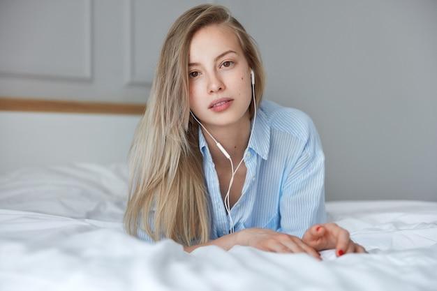 ヘッドフォンが付いているベッドで若いブロンドの女性の肖像画