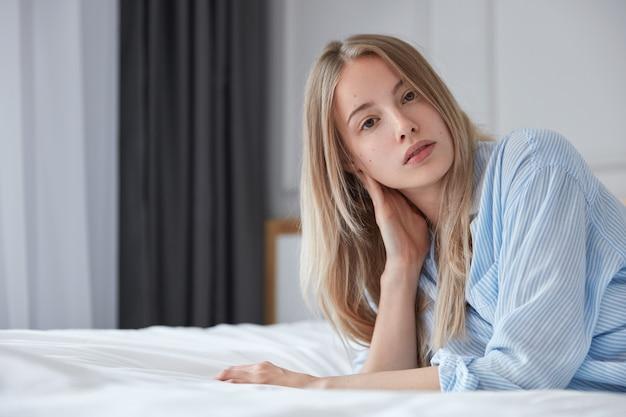 ベッドの中で若いブロンドの女性の肖像画