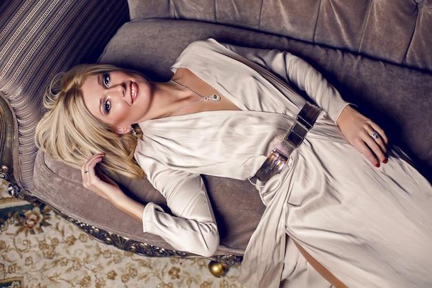 Портрет молодой блондинки, лежащей на диване в длинном платье