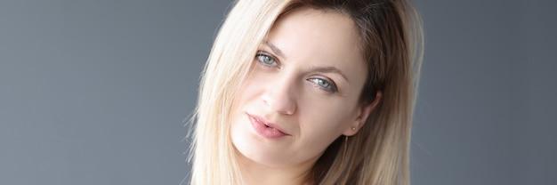 Портрет молодой блондинки на сером фоне концепции ухода за кожей