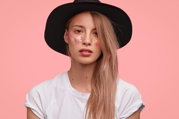 Портрет молодой блондинки с блеском на лице и стильной шляпе