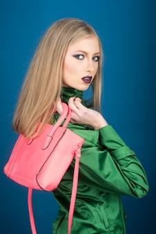 化粧をした若いブロンドの女性の肖像画。美しさとファッション。ピンクの女性のバッグと緑のスーツのファッショナブルな女の子。ファッション、メイクアップ、ショッピングのコンセプト。