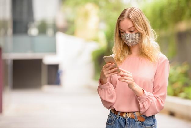 Портрет молодой блондинки с маской для защиты от вспышки вируса короны на улицах города с природой на открытом воздухе
