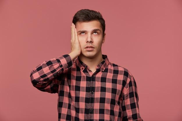 Портрет скучающего молодого человека в клетчатой рубашке, смотрит вверх, стоит на розовом фоне и касается головы, выглядит усталым и грустным.