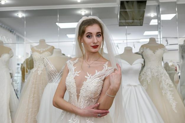 Портрет молодой невесты в свадебном платье в магазине