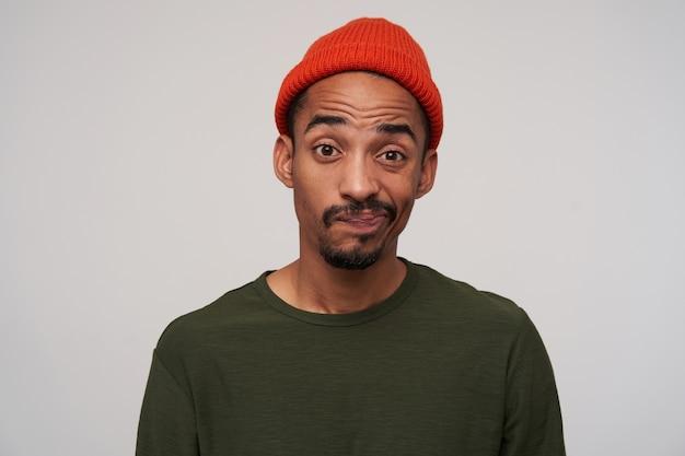 Портрет молодого кареглазого бородатого темнокожего парня, смущенно смотрящего и скручивающего рот, морщащего лоб, позируя на белом