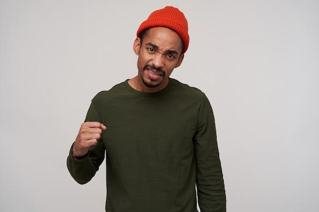 若い茶色の目の暗い肌のブルネットの男性の肖像画、ひげを折りたたんで拳で手を上げ、顔をしかめ、白で隔離