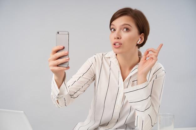 스트라이프 정장 셔츠에 흰색에 앉아있는 동안 그녀의 스마트 폰으로 화상 통화를하는 젊은 갈색 눈의 짧은 머리 갈색 머리 비즈니스 여자의 초상화