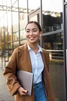 Портрет молодой брюнетки азиатской женщины в наушниках, держащей портативный компьютер во время прогулки по городской улице