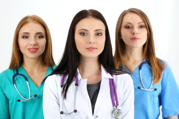 Портрет молодой женщины-доктора брюнет в окружении медицинской бригады, позирует. концепция здравоохранения и медицины.