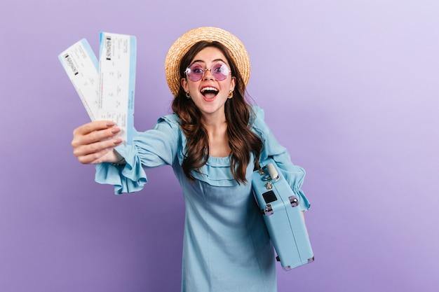 紫色の壁にスーツケースでポーズをとって帽子とメガネの若いブルネットの肖像画。青いドレスを着た女性は、旅行を心から喜んでいます。