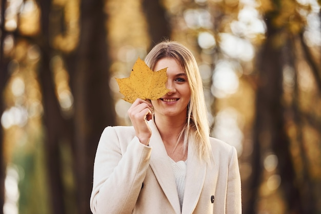 Портрет молодой брюнетки с листом, который находится в осеннем лесу в дневное время.