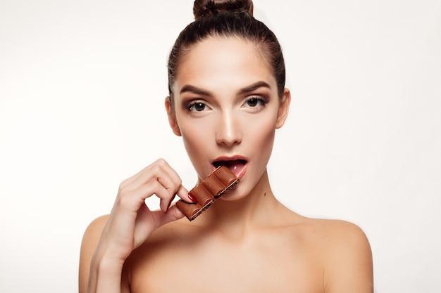 Портрет молодой женщины брюнетки, едящей шоколад