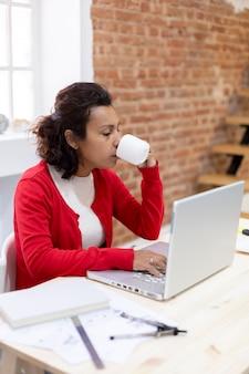 彼女のラップトップで自宅で仕事をしながらコーヒーを飲んでいる若いブルネットの女性の肖像画。テキスト用のスペース。