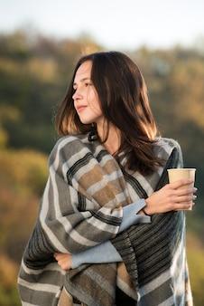 따뜻한 담요와 그의 손에 커피 한 잔에 젊은 갈색 머리 여자의 초상화. 자연미. 수직 프레임.